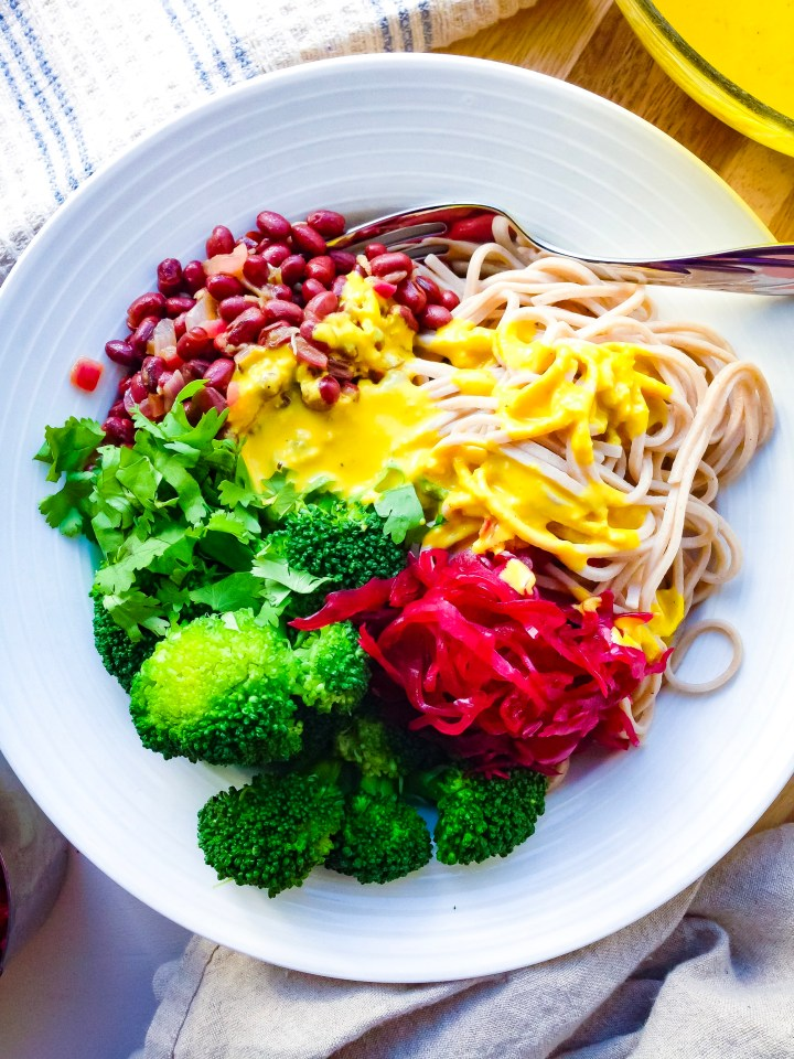 Vegan macrobiotic bowl with soba noodles, marinated adzuki beans, and turmeric tahini sauce recipesteamed broccoli, beet sauerkraut, marinated ad