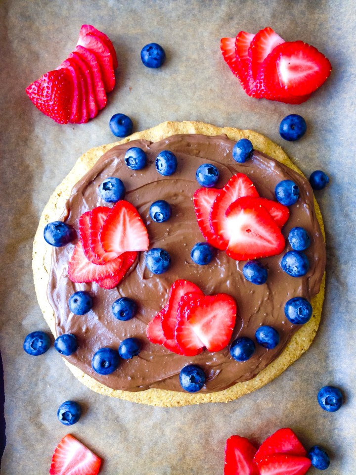 A healthy vegan dessert pizza with a sunflower seed and oat base and a chocolate avocado fudge icing, topped with strawberries and blueberries.