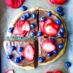 A healthy vegan dessert pizza with a sunflower seed, oat, and maple cookie crust, chocolate avocado frosting, and berries: the ultimate summer dessert!