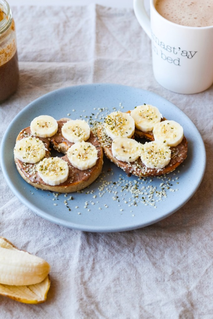 Cinnamon Pecan Almond Butter on toasted bagel, topped with banana and hemp and served with coffee