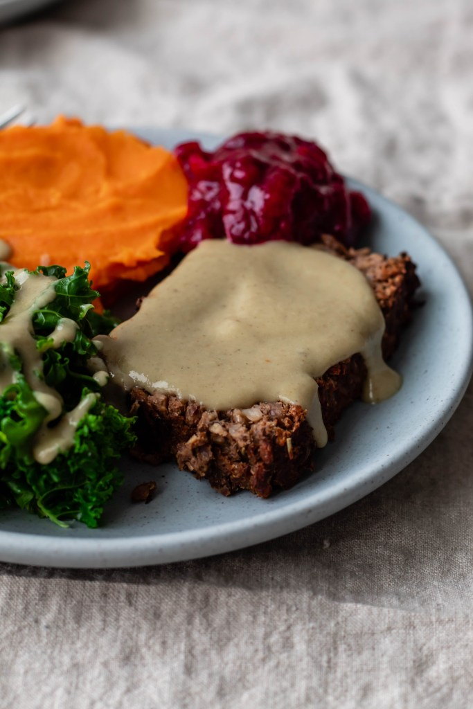 "Homemade ""Beyond Meat"" Meatloaf with Miso Mushroom Gravy (Recipe) on a plate with mashed sweet potato, cranberry sauce, and steamed kale."