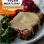a close up of a slice of the meatloaf topped with gravy on a blue plate with mashed sweet potato, steamed kale, and cranberry sauce