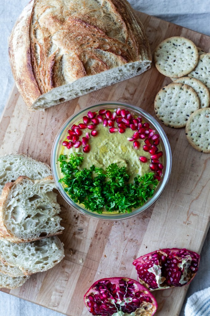 This photo is an overhead shot of vegan Moroccan lentil dip topped with pomegranate and parsley.