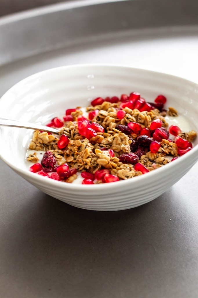 Cranberry, orange, and cardamom granola recipe (A side shot of a bowl of granola and yogurt topped with pomegranate arils.)