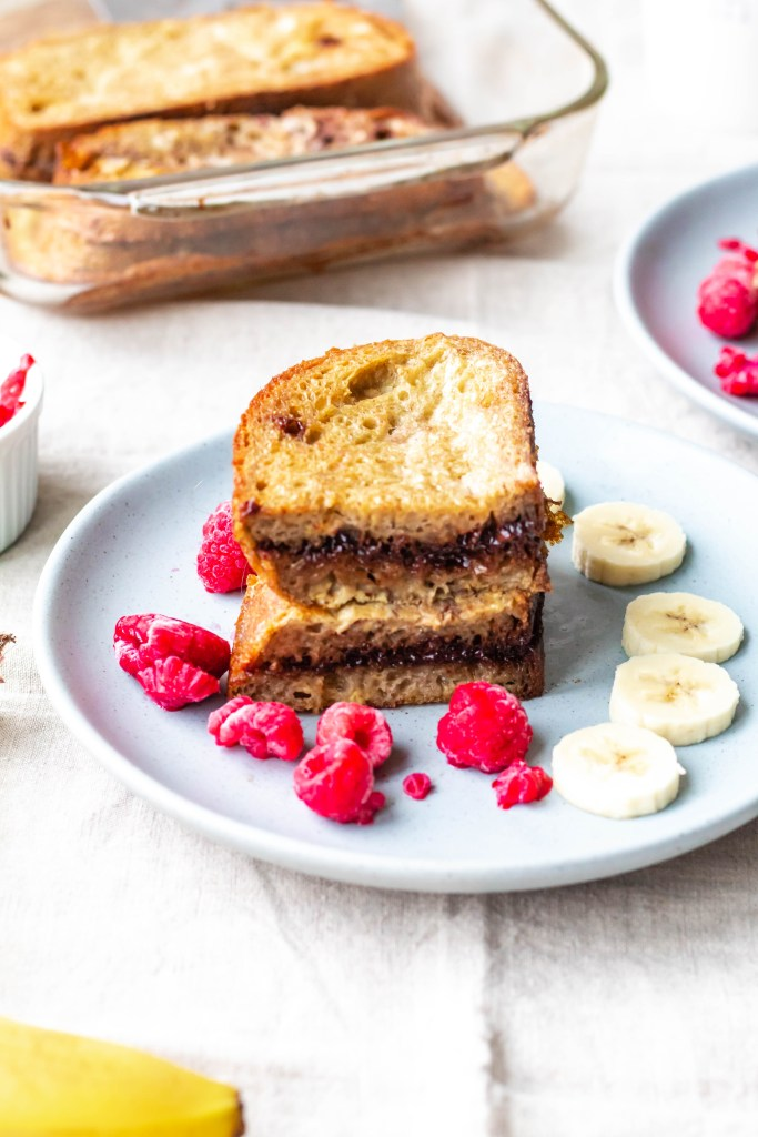 Dairy-Free Nutella French Toast Bake: A shot of a French toast sandwich with raspberries and banana