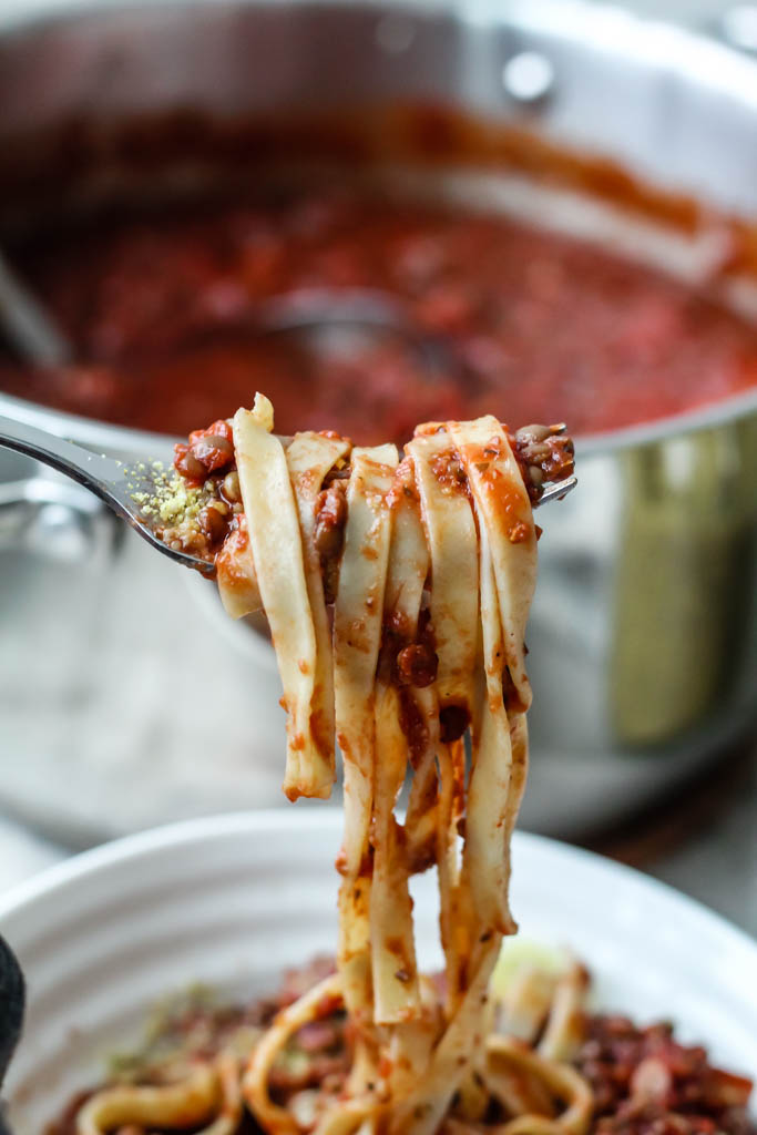 An image showing linguine wrapped around the tines of a fork with vegan bolognese sauce in the background