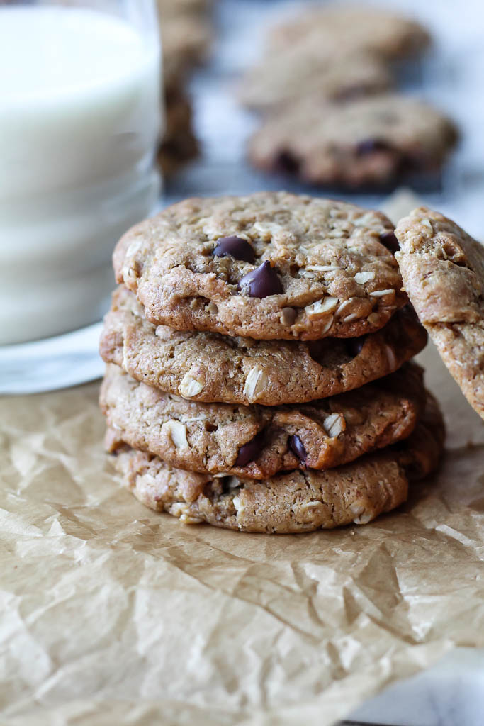 a close up shot of a stack of vegan peanut butter oatmeal chocolate chip cookies with a glass of almond milk in the background.