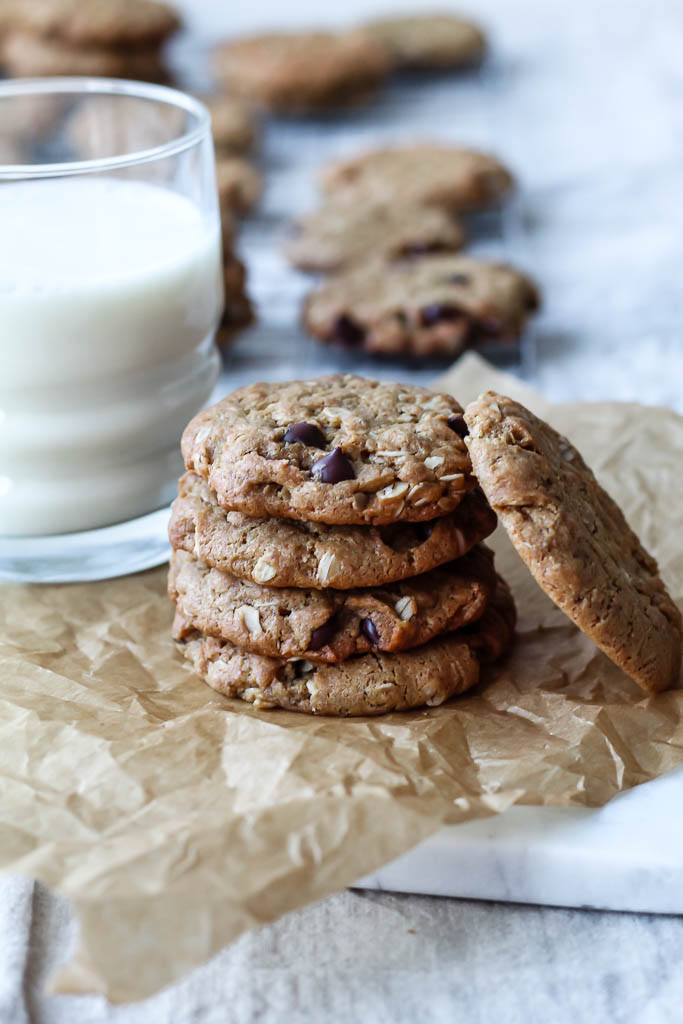 a stack of four vegan peanut butter oatmeal cookies on a crumpled sheet of parchment paper with a glass of almond milk in the background.