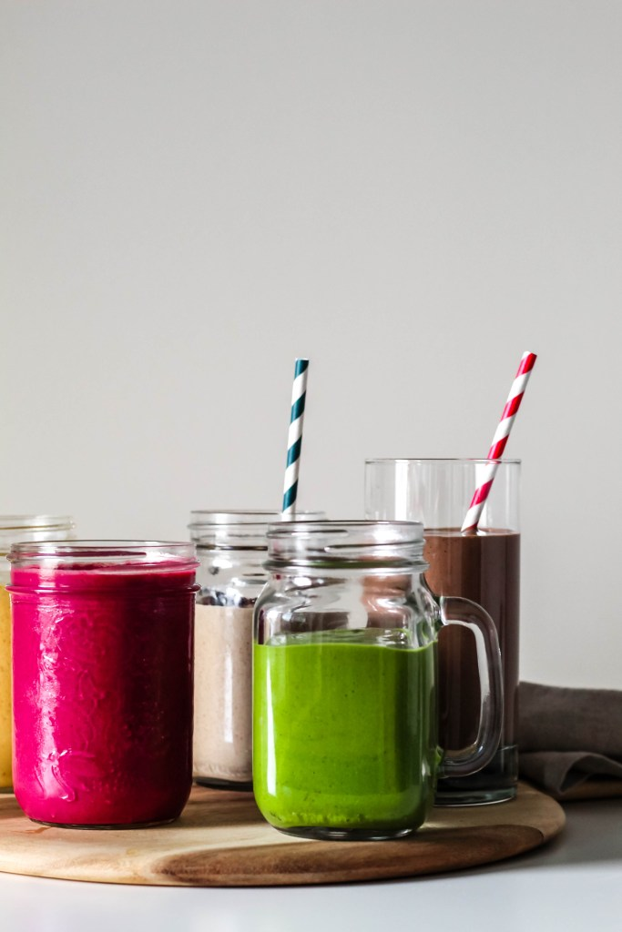 vegan protein smoothies, five ways. this photo shows a green, beet cherry, and chocolate peanut butter smoothie.