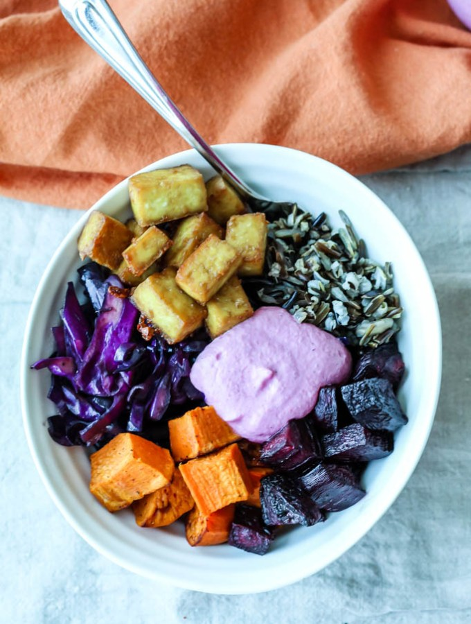 an overhead shot of a wild rice and tofu buddha bowl with roasted beets and sweet potato, purple cabbage, and cranberry sunflower seed sauce in a white bowl with an orange towel around it