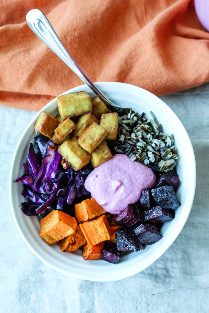 an overhead shot of a buddha bowl containing crispy tofu, wild rice, roasted beets and sweet potatoes, braised purple cabbage, and cranberry sunflower seed sauce.