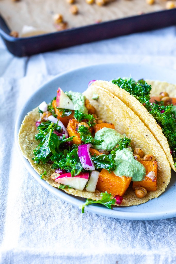 this is a side view of the butternut squash and crispy chickpea tacos showing all of the delicious fillings up close, like bright green kale slaw and sunflower seed parsley sauce!