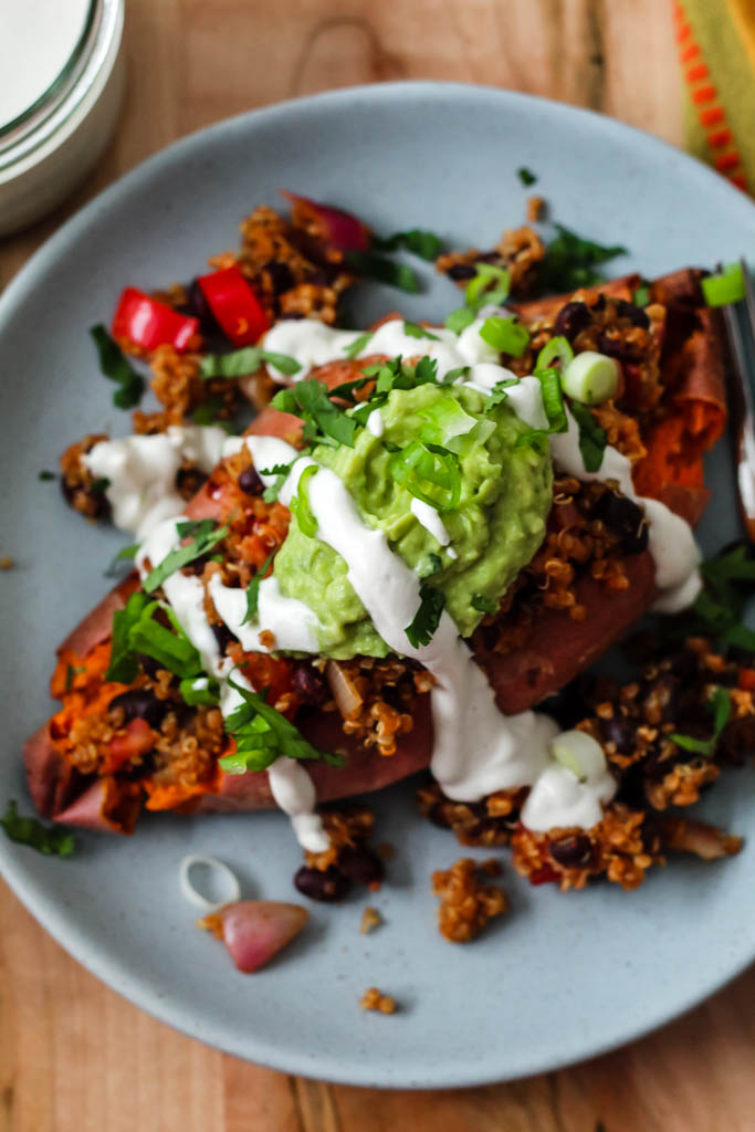 a close up overhead shot of a baked sweet potato fully loaded with the black beans and quinoa, guac, and cashew sour cream, on a blue plate