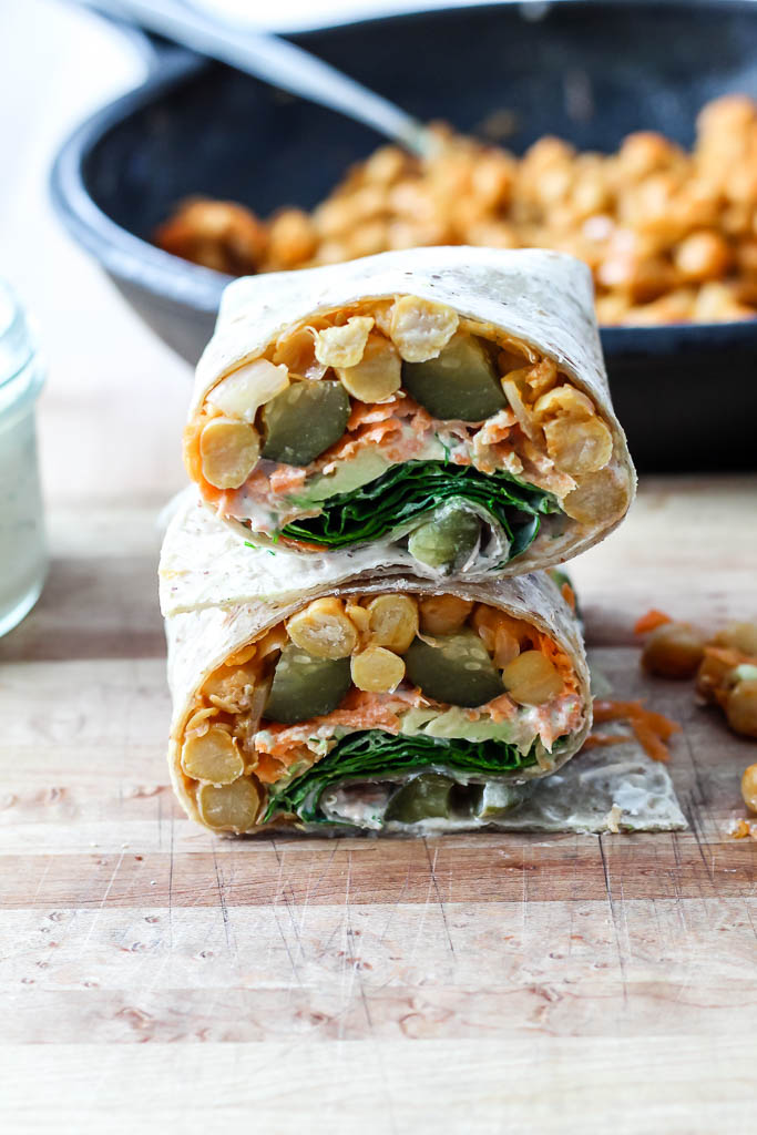 a wrap sliced in half to show all the fillings, with the skillet of buffalo chickpeas in the background