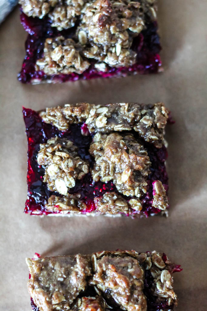 An overhead shot of 3 cranberry oatmeal squares on a piece of brown parchment paper.