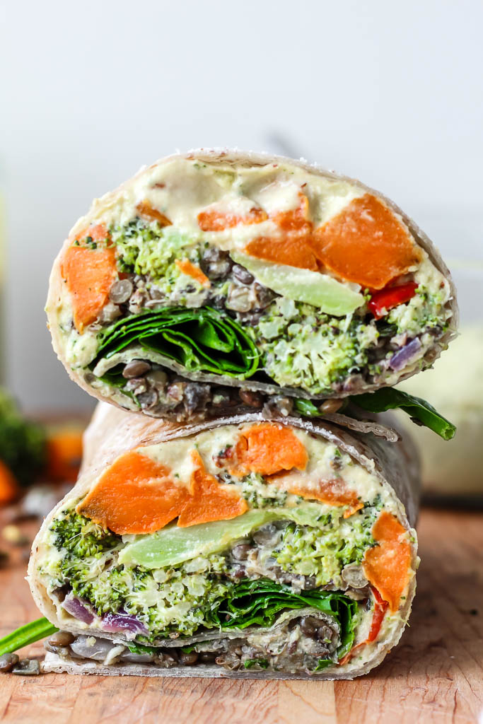 a mediterranean lentil veggie wrap cut in half and stacked to show the fillings, which are lentils, sweet potato, broccoli, spinach, lemon tahini sauce, and hummus, on a wooden cutting board.