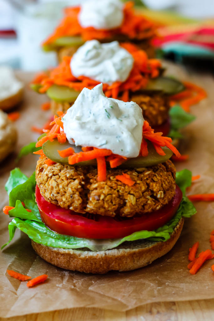 straight on shot of a buffalo chickpea burger on a bun with all the toppings