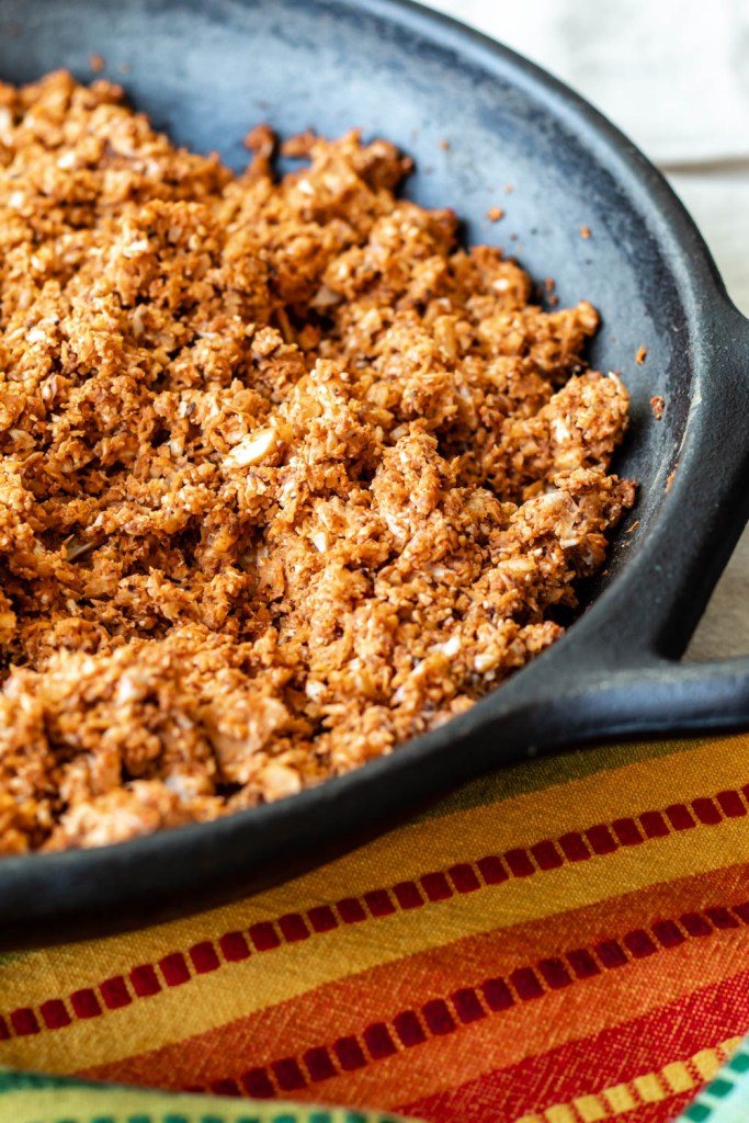 straight on shot of a lodge cast iron skillet full of the cauliflower walnut taco meat