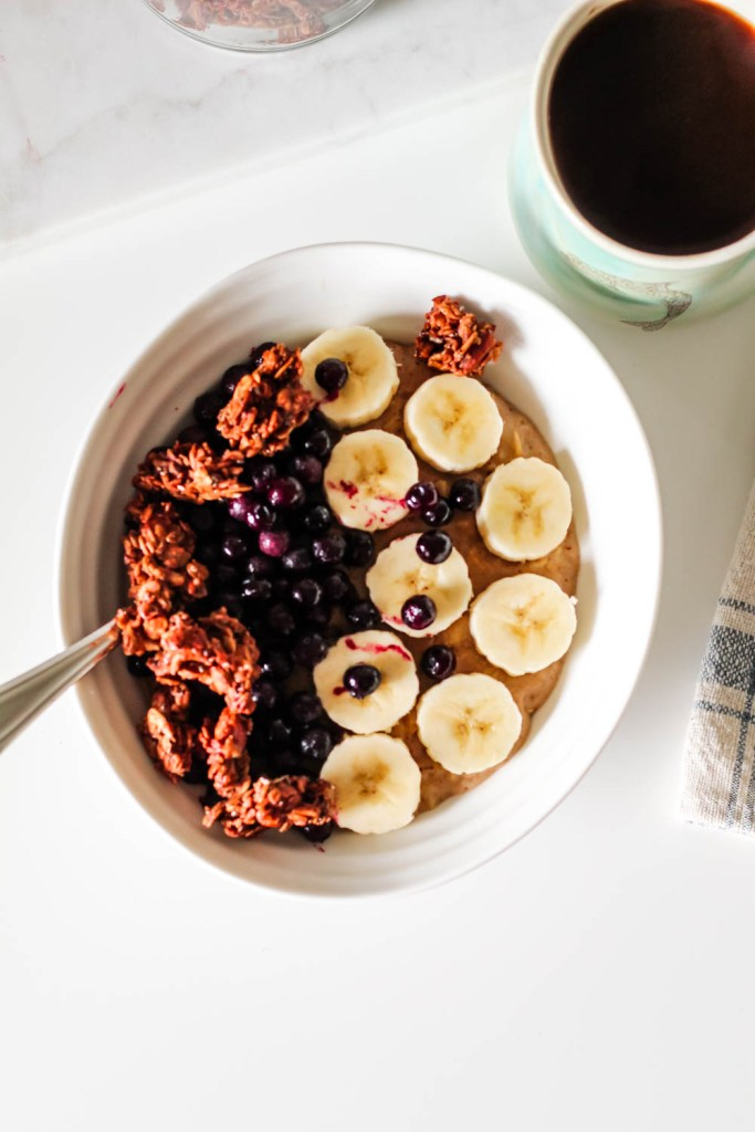 overhead shot of a bowl of the porridge topped with banana, blueberries, and granola