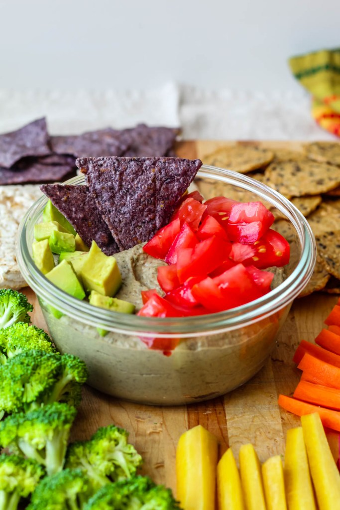 straight on shot of the black bean hummus in a clear glass container topped with avocado, tomato, and tortilla chips