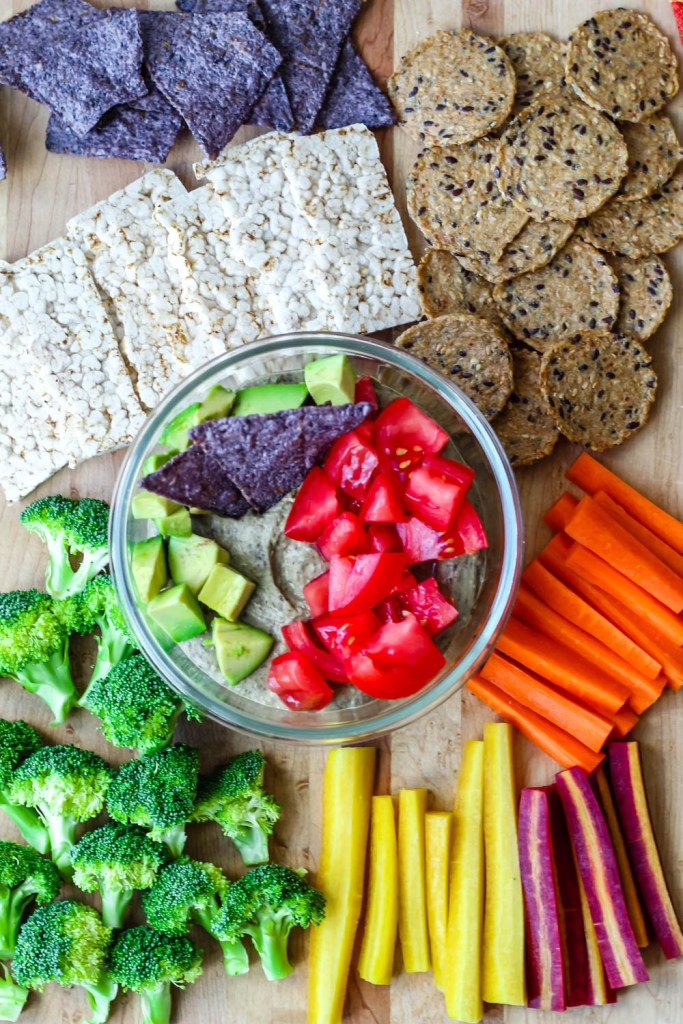 overhead shot of the black bean hummus in a container topped with avocado, tomatoes, and surrounded by crackers and vegetables.