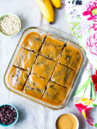an overhead photo of the entire vegan chocolate banana cake, sliced, in the pan, surrounded by a floral towel, a small dish of oats, banana, and chocolate chips for decoration