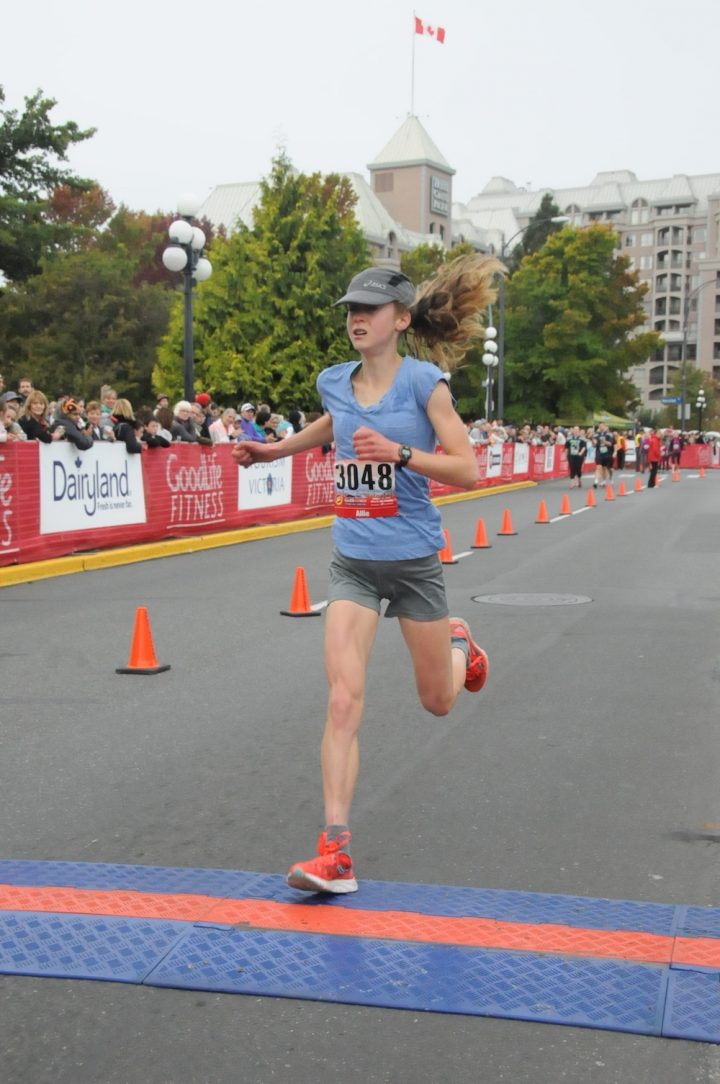 an image of the author crossing the finish line of a half marathon