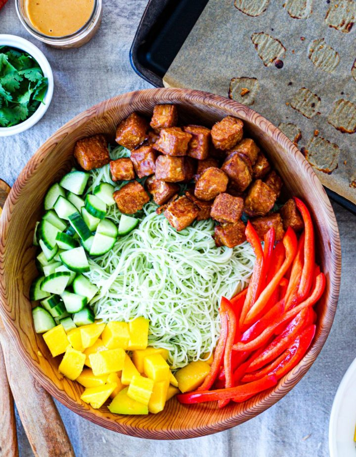 overhead shot of the salad in a large serving bowl with peanut tempeh, vegetables, and mango on top