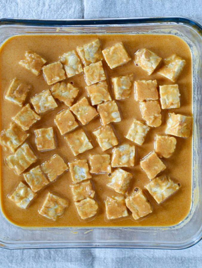 an overhead shot of the peanut sauce-coated tempeh cubes in a square dish