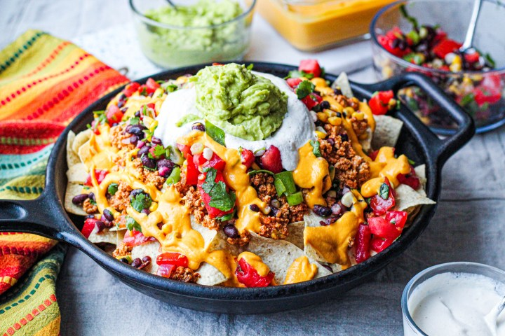 a straight on shot of the vegan nachos in a cast iron skillet for serving