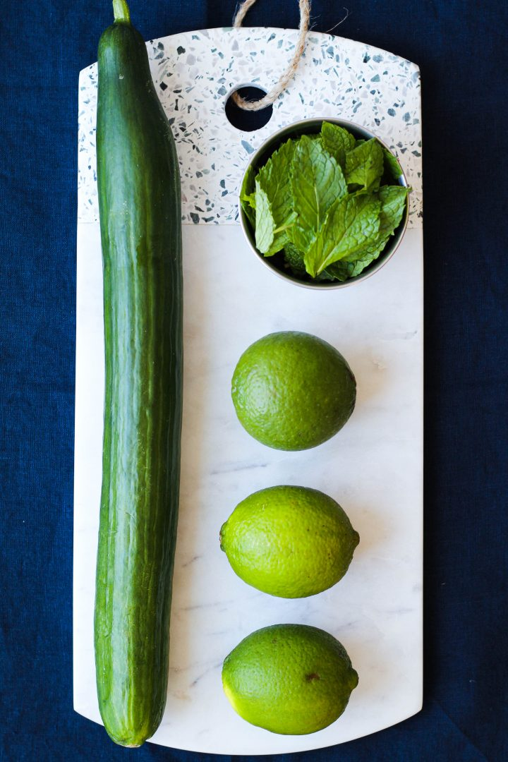 an ingredient shot: a cucumber, limes, and mint on a marble board