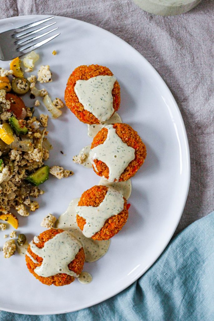 overhead shot of sweet potato quinoa cakes with lemon dill tahini sauce on a white plate