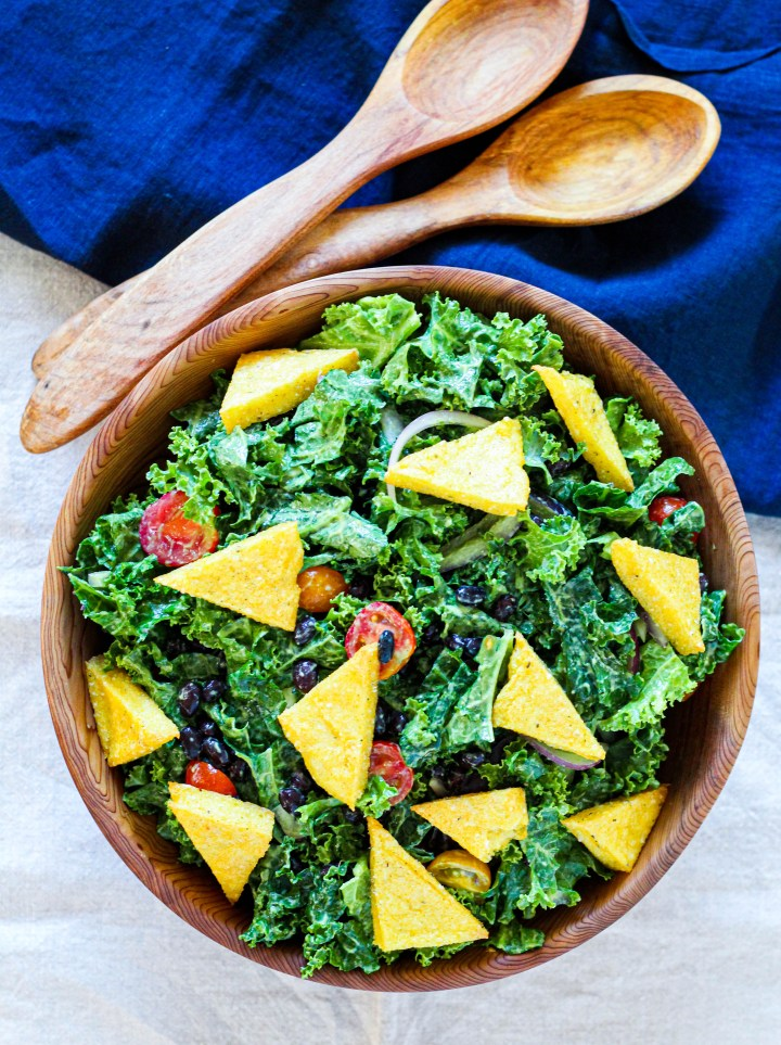 overhead shot of avocado kale salad in wooden salad bowl with polenta croutons on top