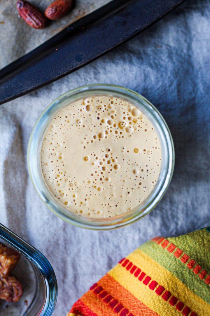 overhead shot of the lemon tahini sauce in a glass jar