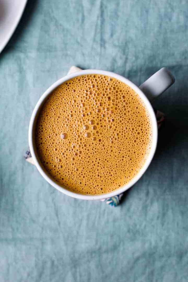 overhead shot of a clay mug of the cashew pumpkin spice latte on a blue background