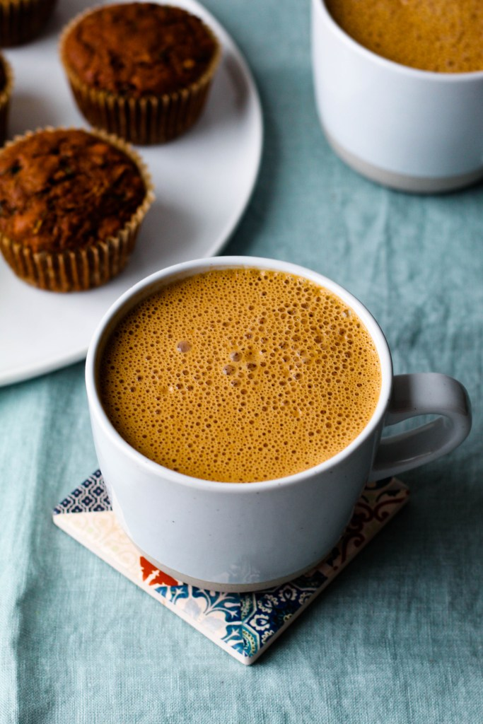 angled overhead shot of a cashew pumpkin spice latte in a light blue-grey mug with a plate of muffins in the background