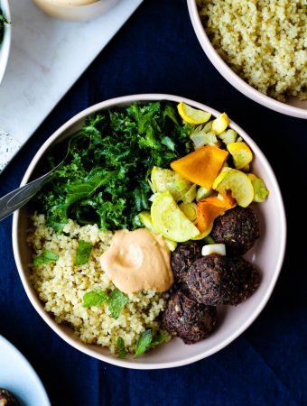 overhead shot of one of the bowls with lentil meatballs, quinoa, kale, roasted vegetables, and roasted red pepper tahini sauce