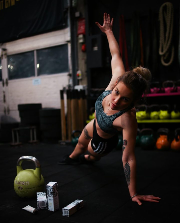 woman in a side plank position in a gym with a kettlebell