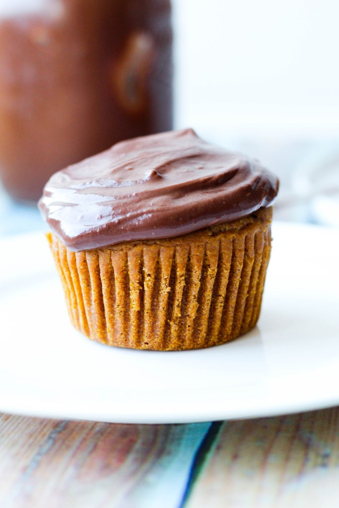 straight on shot of one pumpkin spice cupcake topped with hot fudge icing