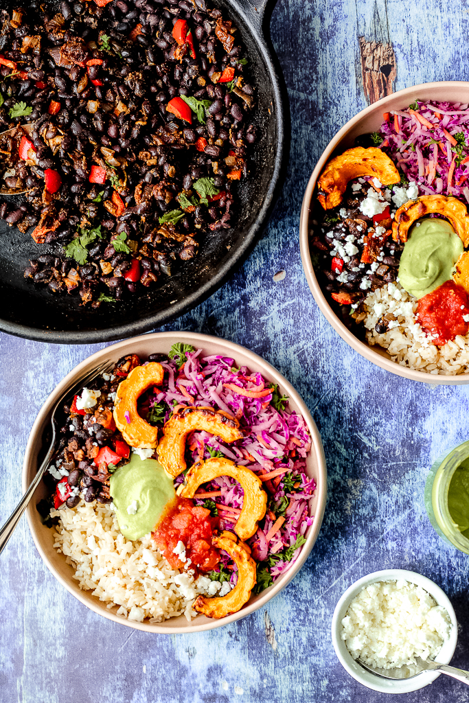 an overhead shot of two burrito bowls and a skillet of seasoned black beans on a blue backdrop