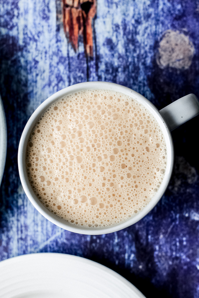 an overhead shot of the white hot chocolate in a blue mug against a dark blue backdrop