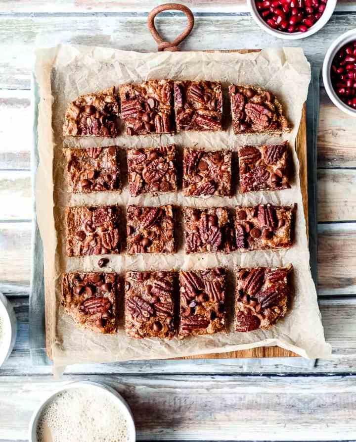 overhead shot of the caramel pecan bars on a wooden board and parchment paper against a wood backdrop