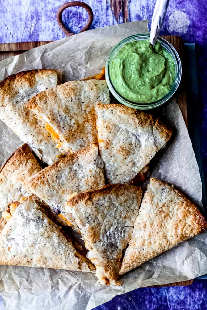 an overhead shot of the quesadillas, sliced into triangles, on a wooden tray with a jar of the dipping sauce beside