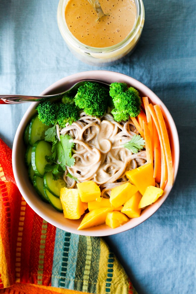 overhead shot of one bowl of peanut butter noodles garnished with carrots, mango, and broccoli