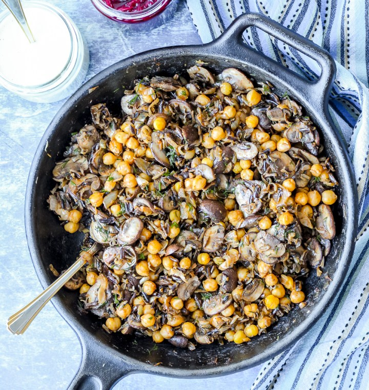 an overhead shot of chickpeas, white beans, and mushrooms mixed together in a skillet