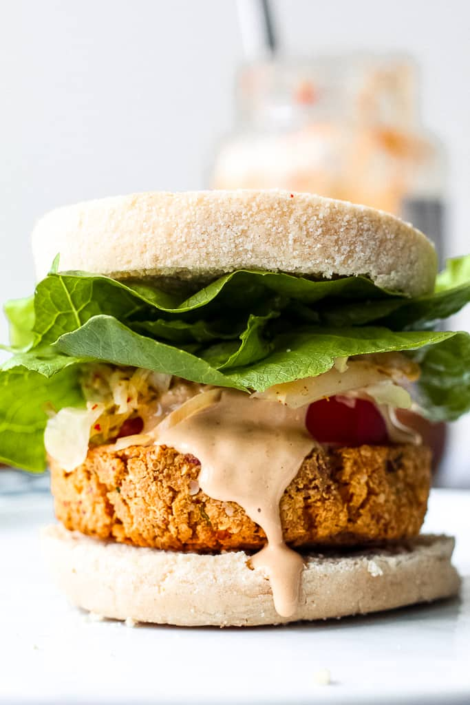 close up of a tofu burger on a white plate with sriracha aioli dripping down the side