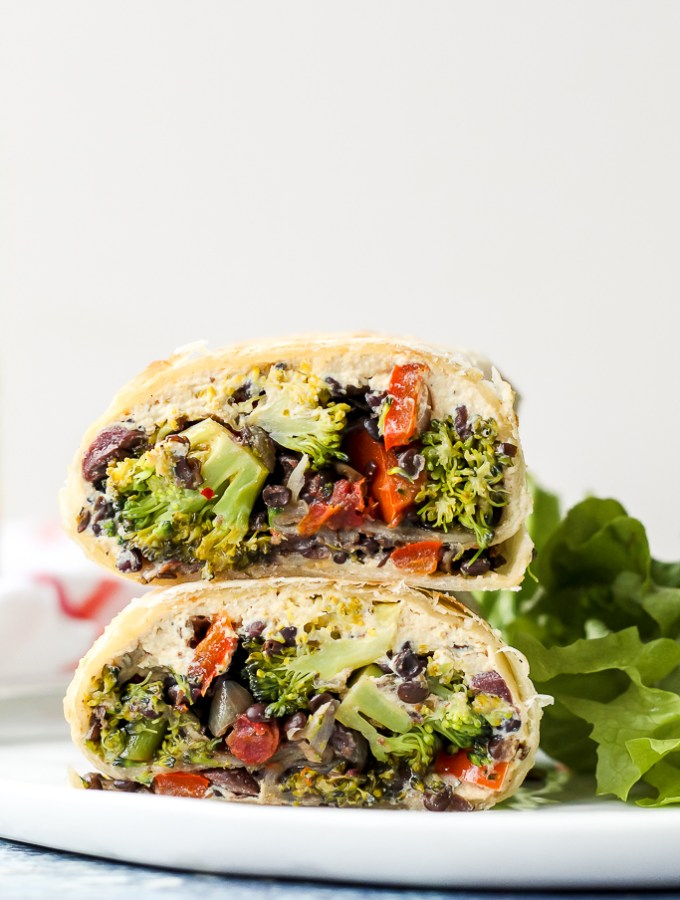 a straight on shot of one of the burritos, sliced in half and stacked one half on top of the other, on a white plate with a green salad beside it