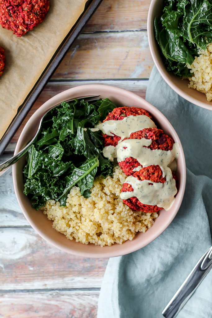 overhead shot of a beet falafel bowl against a wood backdrop with a blue towel spread out for decoration