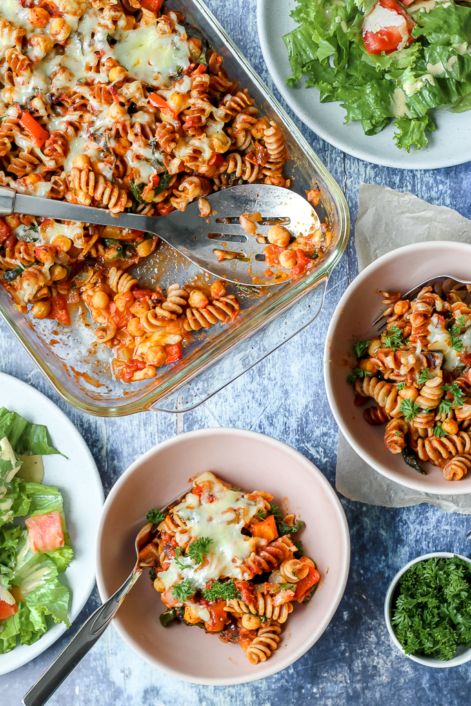an overhead shot of two bowls of chickpea pasta bake and the large pan of the casserole on a blue backdrop