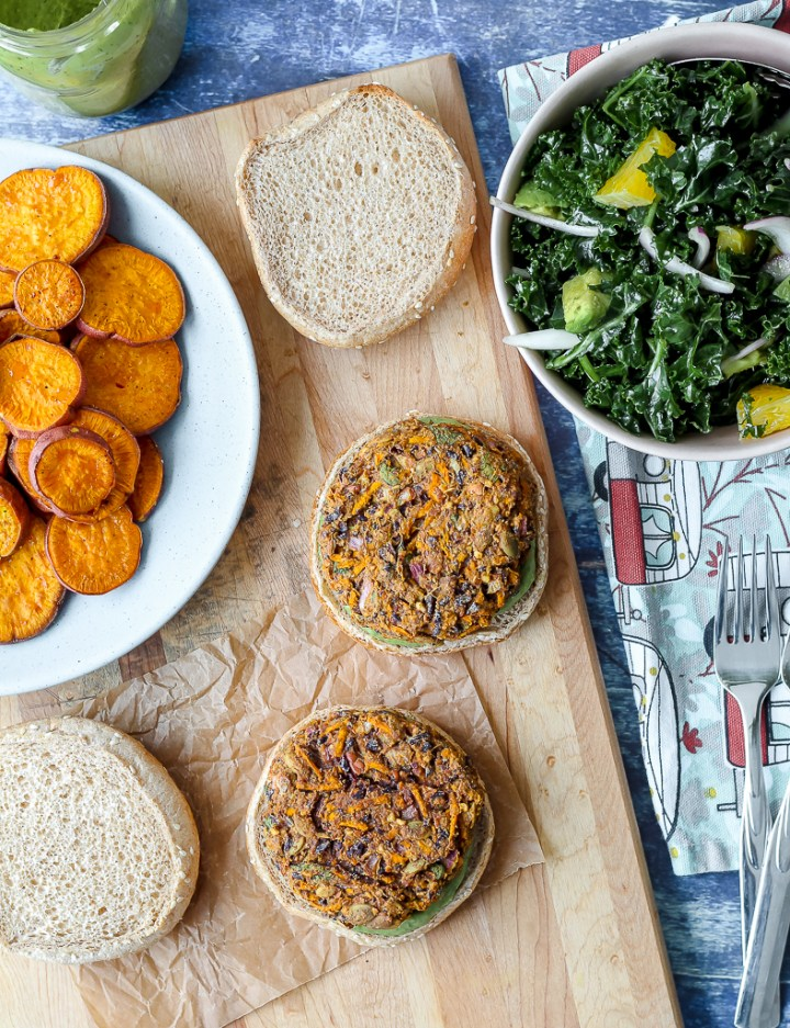 an overhead shot of two veggie burgers on whole grain buns on a wooden board with a dish of roasted sweet potato slices and a bowl of kale salad around them